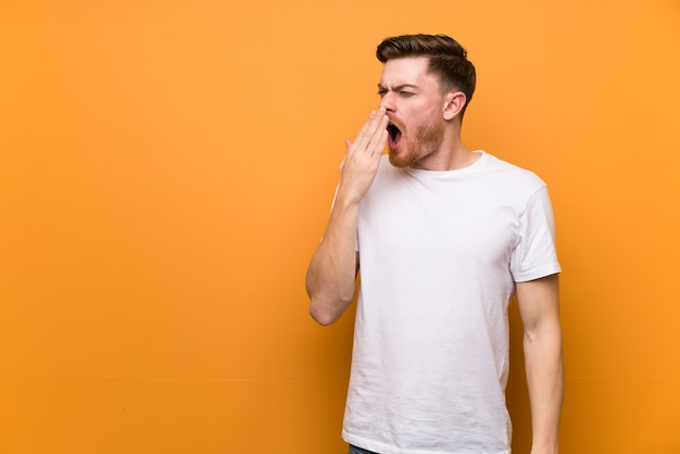 Redhead man brown wall yawning and covering wide open mouth with hand