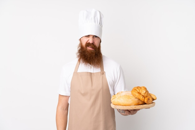Redhead man in chef uniform. male baker holding a table with several breads with sad expression