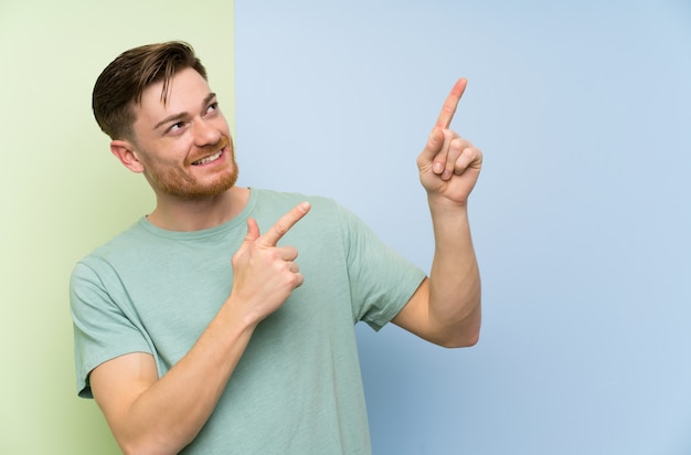 Redhead man over colorful wall pointing with the index finger a great idea