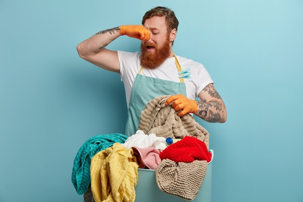 Redhead man covers nose, feels bad smell, disgusting aroma from dirty laundry, going to wash with liquid powder, wears rubber gloves and apron, busy doing housework during weekend. what stench!