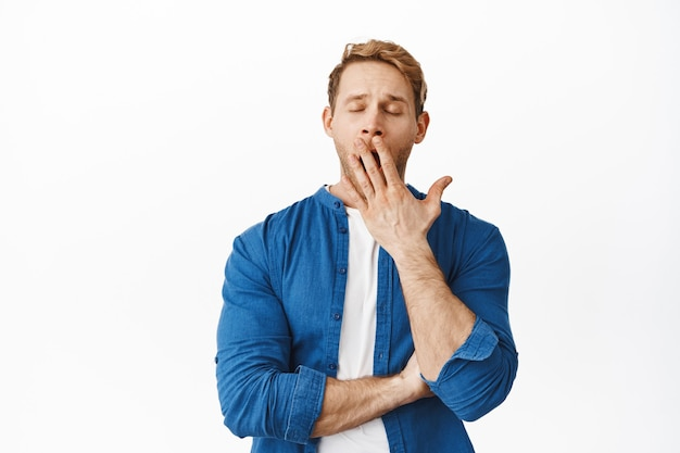 Redhead man feels tired and yawns, covers mouth with palm and close eyes, exhausted or bored, stands against white wall in casual clothes