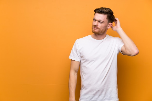 Redhead man having doubts while scratching head