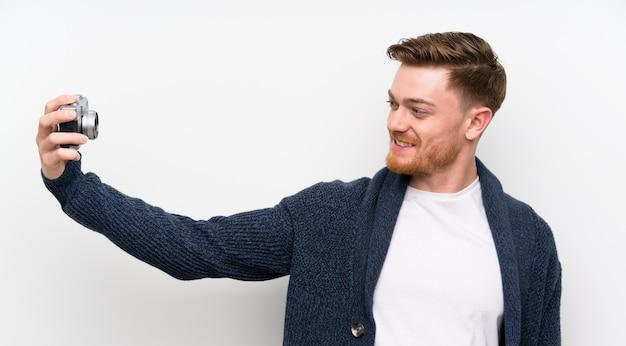 Redhead man holding a camera