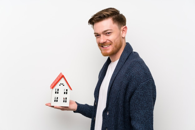 Redhead man holding a little house