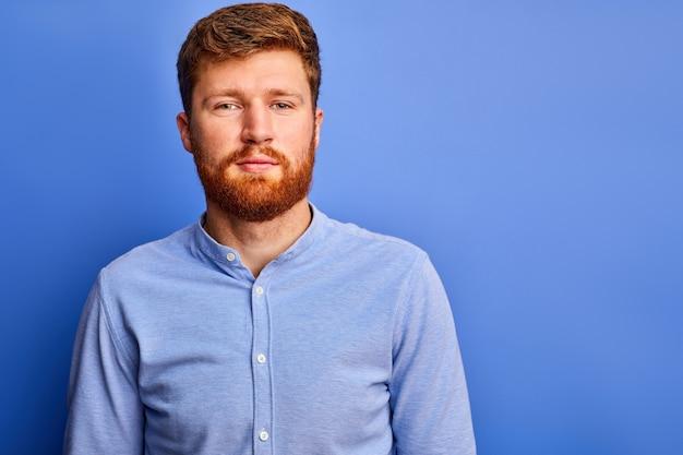 Рыжий мужчина в строгой рубашке смотрит в камеру, приятный бородатый парень изолирован над синим пространством