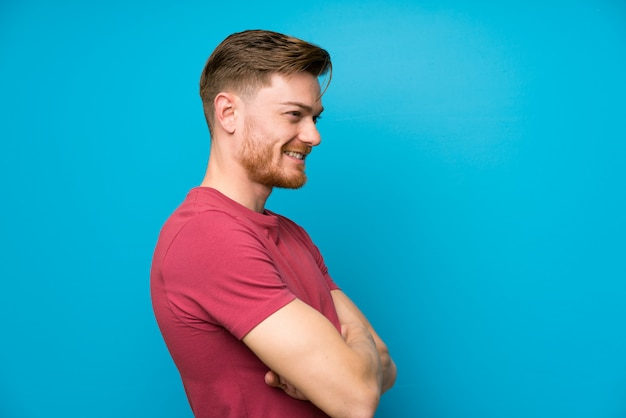 Redhead man on isolated blue wall standing and looking to the side