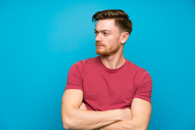 Redhead man on isolated blue wall standing and looking side