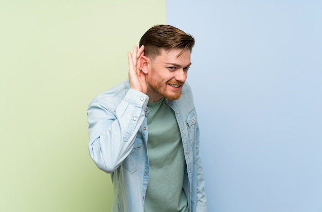 Redhead man listening to something by putting hand on the ear