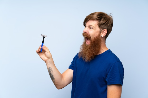 Redhead man shaving his beard over isolated blue wall