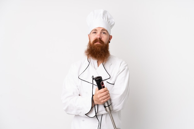 Redhead man using hand blender over isolated white wall keeping arms crossed