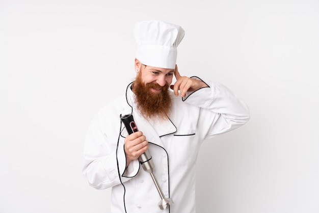 Redhead man using hand blender over isolated white wall laughing