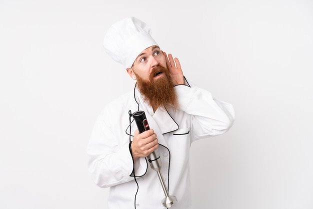 Redhead man using hand blender over isolated white wall listening something