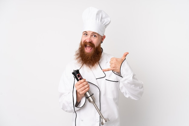 Redhead man using hand blender over isolated white wall making phone gesture