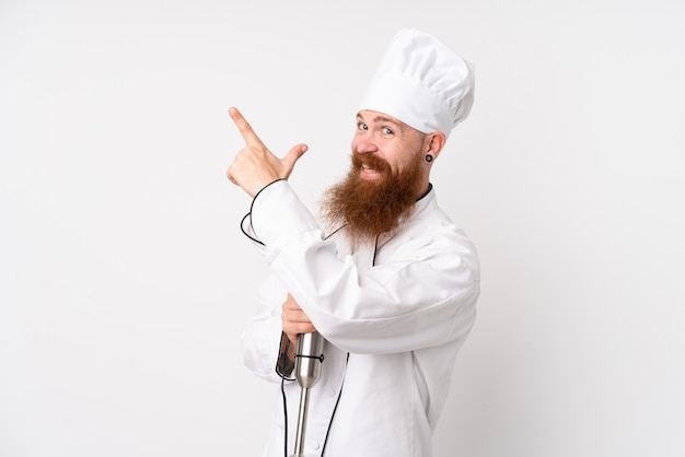 Redhead man using hand blender over isolated white wall pointing with the index finger a great idea