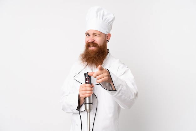 Redhead man using hand blender over isolated white wall points finger at you