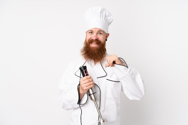 Redhead man using hand blender over isolated white wall proud and self-satisfied