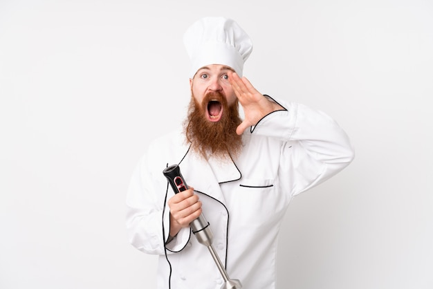 Redhead man using hand blender over isolated white wall shouting with mouth wide open