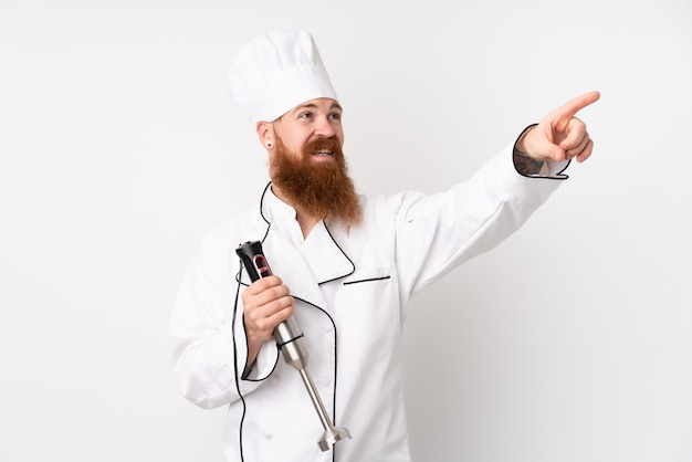 Redhead man using hand blender over isolated white wall touching on transparent screen