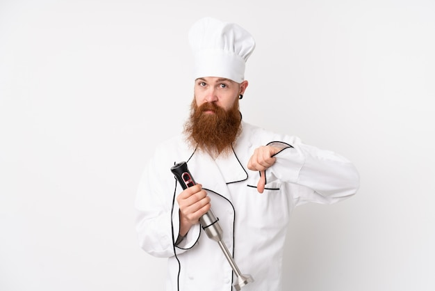 Redhead man using hand blender over white wall showing thumb down sign