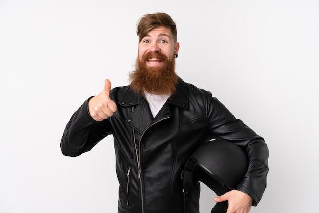 ジェスチャーの親指を与える分離の白い壁にオートバイのヘルメットを保持している長いひげを持つ赤毛の男