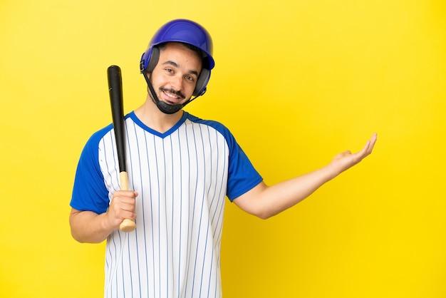 Рыжий мужчина с длинной бородой держит футбольный мяч над изолированной фиолетовой стеной с удивленным выражением лица