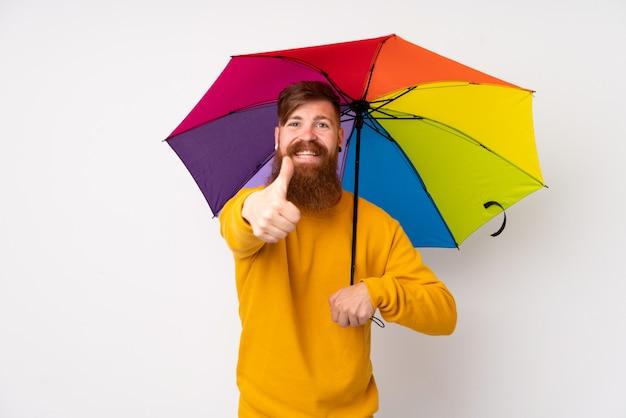Рыжий мужчина с длинной бородой держит зонтик над белой стене, давая недурно жест