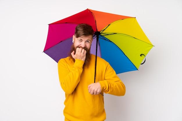 Рыжий мужчина с длинной бородой держит зонтик над белой стеной нервной и страшно