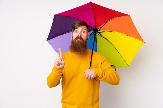 Рыжий мужчина с длинной бородой держит зонтик над белой стене, указывая указательным пальцем отличная идея