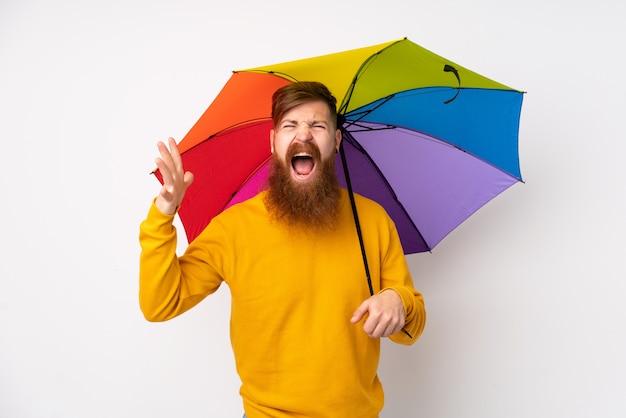 Рыжий мужчина с длинной бородой держит зонтик над белой стеной несчастным и разочарованным чем-то