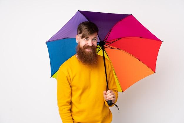 Рыжий мужчина с длинной бородой держит зонтик над изолированной белой стеной