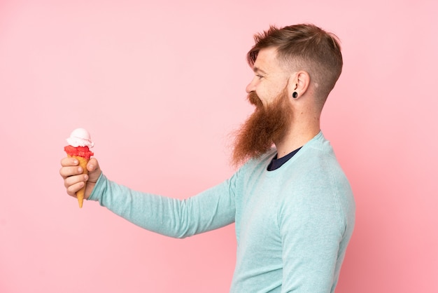 Redhead man with long beard holding a cornet ice cream over isolated pink wall with happy expression
