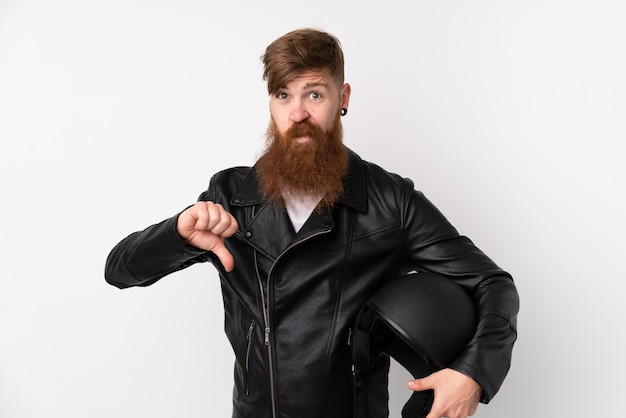 Redhead man with long beard holding a motorcycle helmet over isolated white wall showing thumb down sign