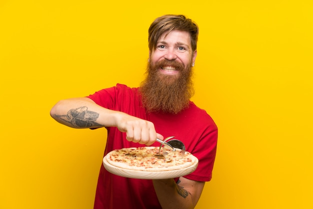 Redhead man with long beard holding a pizza over isolated yellow wall