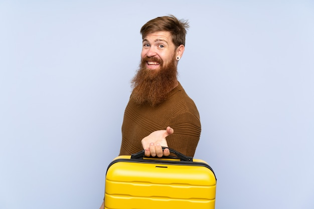 Redhead man with long beard holding a suitcase smiling a lot