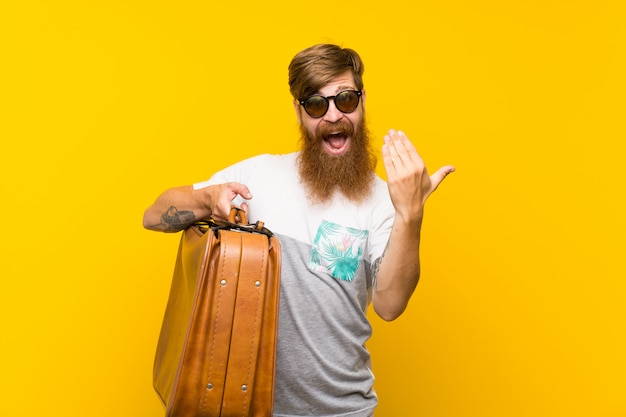 Redhead man with long beard holding a vintage briefcase inviting to come with hand. happy that you came