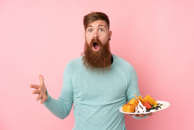 Redhead man with long beard holding waffles over isolated pink wall with shocked facial expression