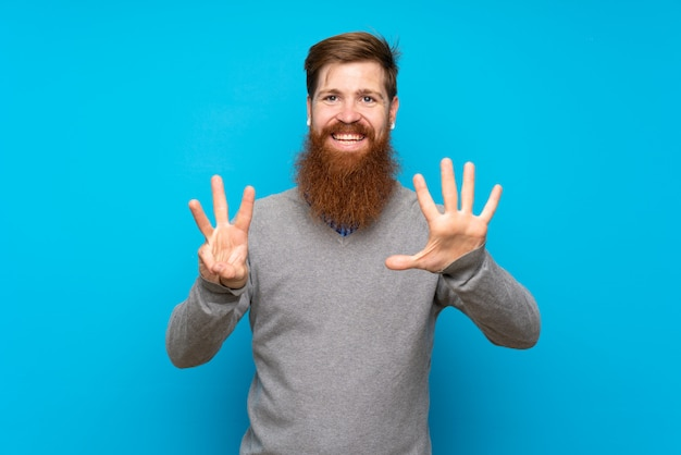 Redhead man with long beard over isolated blue counting eight with fingers