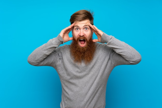 Redhead man with long beard over isolated blue with surprise expression