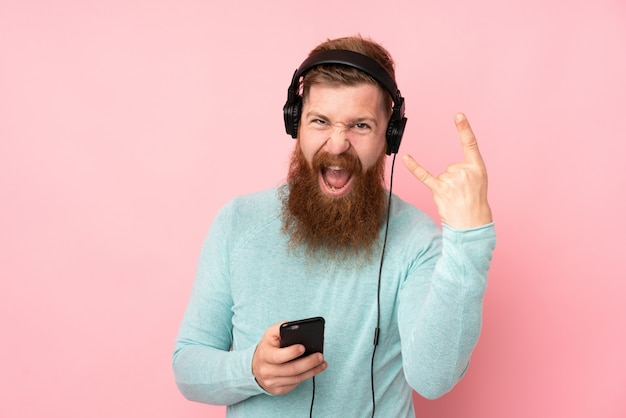 Redhead man with long beard over isolated pink wall listening music making rock gesture