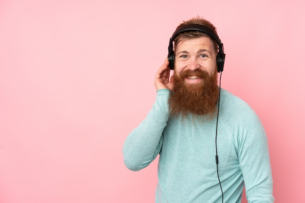 Redhead man with long beard over isolated pink wall listening music