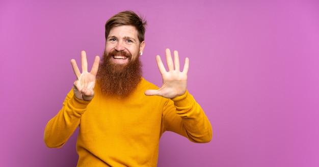 Redhead man with long beard over isolated purple counting eight with fingers
