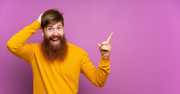 Redhead man with long beard over isolated purple surprised and pointing finger to the side
