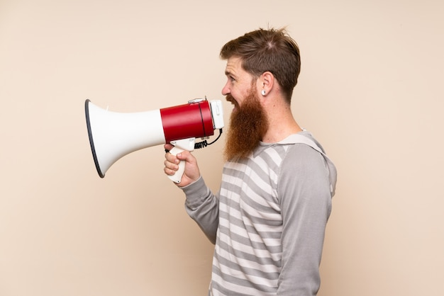 Redhead man with long beard over isolated wall shouting through a megaphone