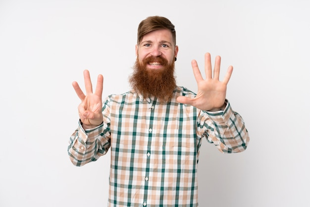 Redhead man with long beard over isolated white wall counting eight with fingers