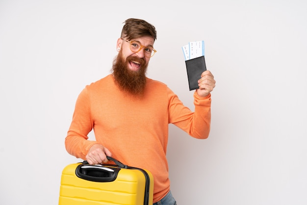 Redhead man with long beard over isolated white wall in vacation with suitcase and passport
