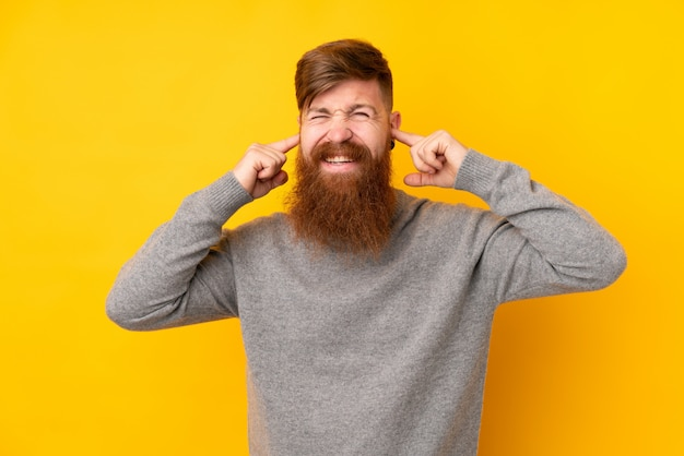 Redhead man with long beard over isolated yellow wall frustrated and covering ears