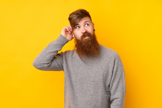 Redhead man with long beard over isolated yellow wall having doubts