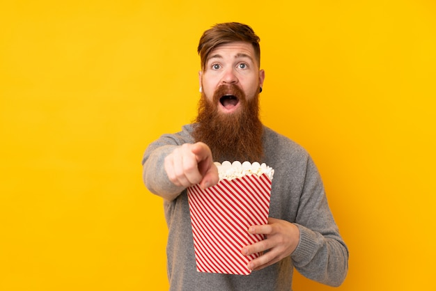 Redhead man with long beard over isolated yellow wall holding a big bucket of popcorns while pointing front