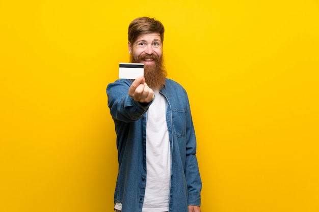 Redhead man with long beard over isolated yellow wall holding a credit card