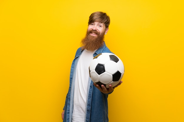 Redhead man with long beard over isolated yellow wall holding a soccer ball